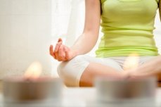 Woman meditating at home, preparing for her first visit with a gastroenterologist