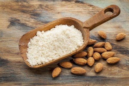 Photo of almond flour and whole, raw almonds. Almonds are a gluten-free food often used as a healthy snack and in baking.