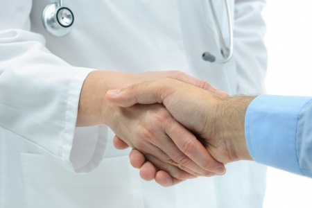 A doctor and his patient shaking hands