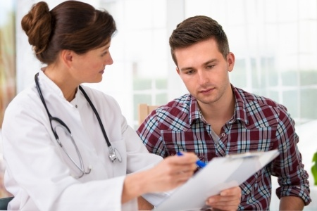 A doctor talking to her male patient during an office visit