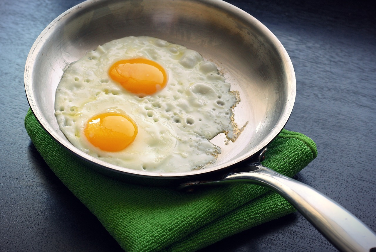 A photo of two eggs in a frying pan. During the elimination phase of this autoimmune diet, eggs are removed from the diet.