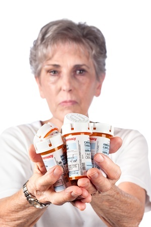 A woman holding several bottles of prescription drugs