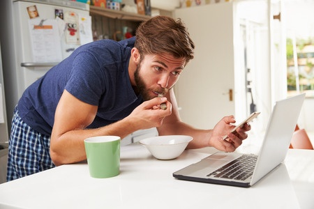 Photo of a young man not eating mindfully. He is eating breakfast while standing and using his mobile phone and laptop.